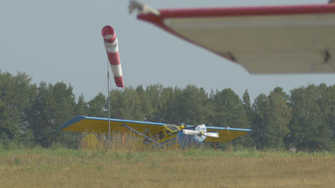 Red-white windsock near airplane on the field Footage