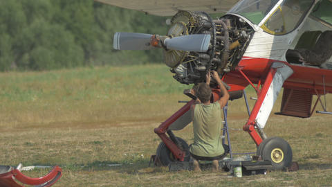 The engineer repairing the engine of the plane on the glade Footage
