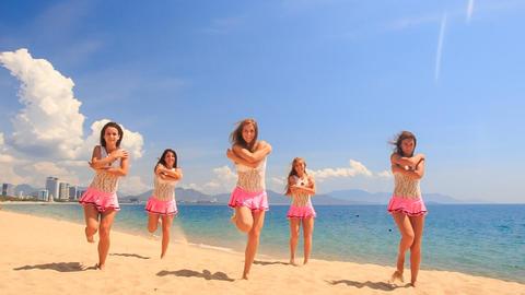 cheerleaders dance bend in poses on beach against sea Footage