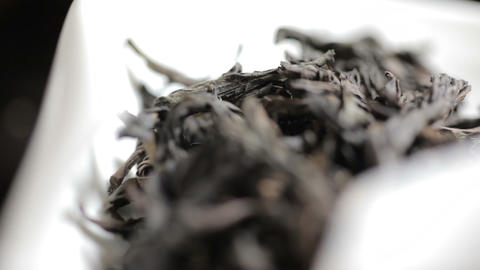 Close up shot of aromatic black loose tea leaves pile on light background Footage