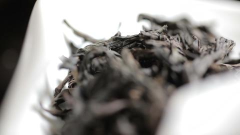 Close up shot of aromatic black loose tea leaves pile on light background Footage