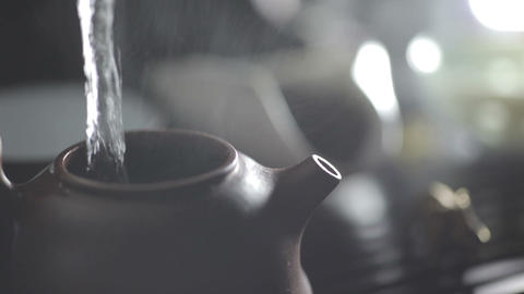 Water pouring into clay teapot Footage