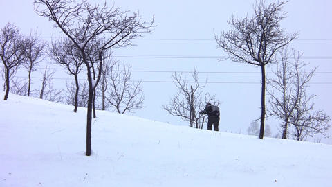 Tourists who go backpacking climb a snowy slope through a deserted orchard and c Footage