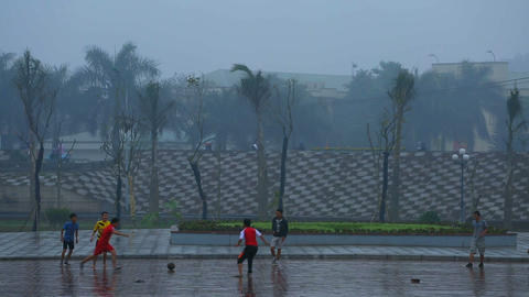 Hanoi, Vietnam - 13 March 2015: Boys playing football (soccer) under the rain Footage