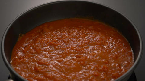 Bubbling hot tomato sauce for pasta, cooking in pan with wooden spatula ビデオ