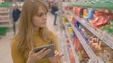 Attractive young woman in the store checking list of products on touch pad Footage