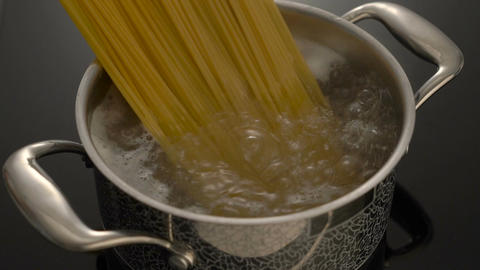Cooking spaghetti in boiling water in pot on electric stove Footage