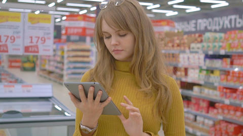 Lovely young woman in supermarket checking shopping list on tablet Live Action