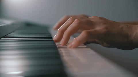 Woman's hands on the keyboard of the piano closeup Footage