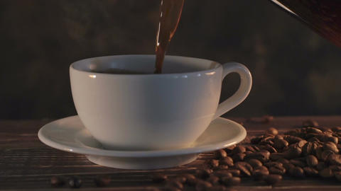 Hot coffee with coffee beans on wooden table Footage
