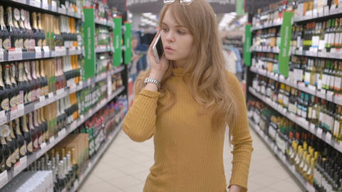 Cute woman with mobile talking and deciding what wine to buy in supermarket Footage
