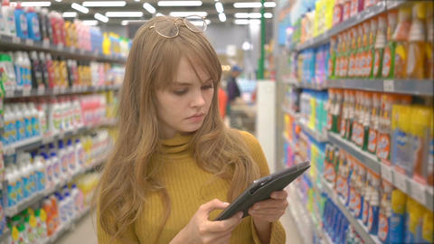 Young pretty girl shopping in hypermarket and looking for information about the Footage
