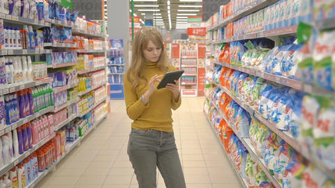 Lovely young woman in supermarket checking shopping list with tablet Live Action