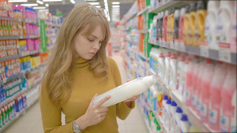 Attractive young blond woman choosing detergent in laundry section of ビデオ