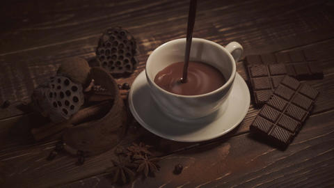 pouring hot chocolate with anise and cinnamon sticks on dark wooden table Footage