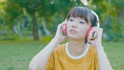 woman smile happily and use phone listen music in the park ビデオ