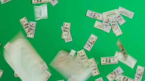 One hundred dollar bills are falling against a green background Footage