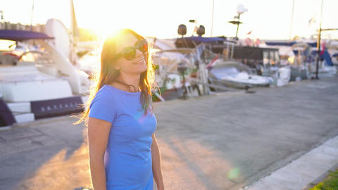 Woman in sunglasses walking along the dock with a lot of yachts and boats at Footage