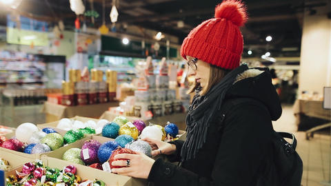 Young attractive caucasian girl with glasses and a red hat chooses the balls for Archivo
