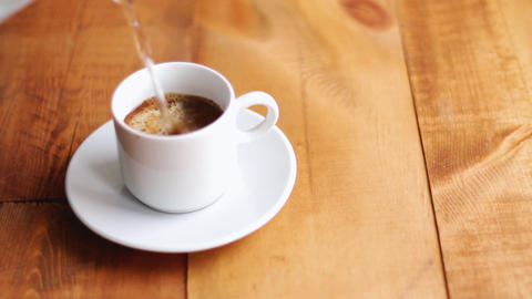 a cup of coffee is filled with hot coffee on wooden background ビデオ