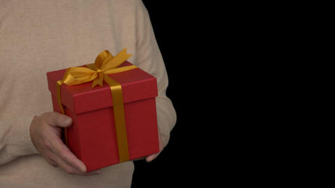 Caucasian man in beige sweater is holding a red gift box in hands. Half turn Footage