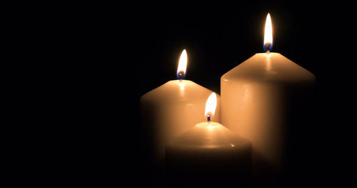 Candles burning on black background Image
