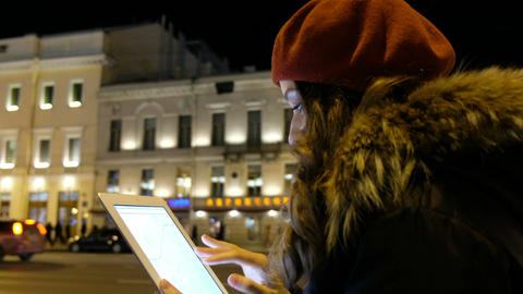 Attractive girl looks out the tablet and waiting for the bus in the evening in Footage