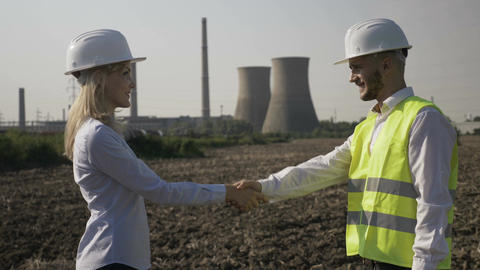 Successful businesswoman and handsome engineer shaking hands agreeing project Footage