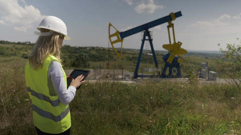 Oil forewoman engineer using a tablet pc to check maintenance schedule for oil Live Action