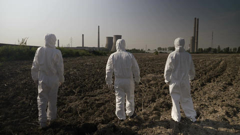 Employees ecologists team in hazmat suits looking at contaminated environment Footage