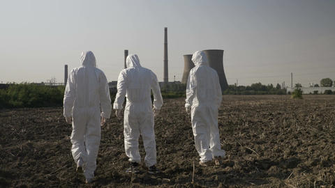 Scientists dressed in hazmat suits carefully walking across a contaminated field Footage