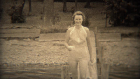 1938: Cute woman walking on lake dock in conservative 30s style swimwear Live Action