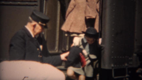 1937: Train conductor helping mother and daughter exit railroad train Live Action