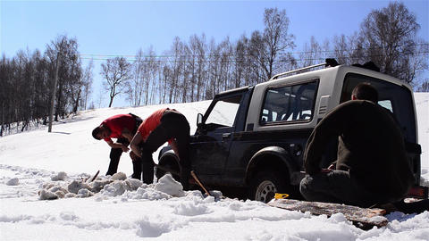 Men shoveling snow out from under a car remained bogged in the middle of the roa Footage