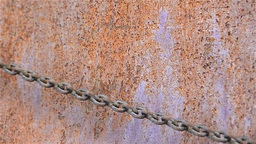 Rusty chain caught over a rusty metal wall 2 Live Action