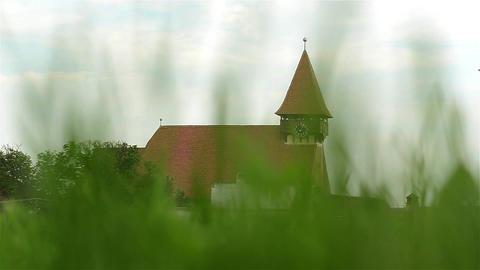 Old village church seen through wires tall green grass 1 Footage