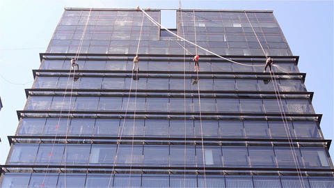Team of workers that cleans exterior windows of a tower block, they are all down Footage