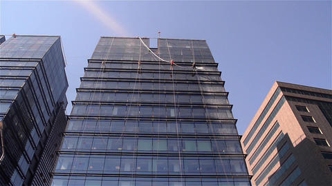 Team of workers that cleans exterior windows of a tower block, they are all down Live Action