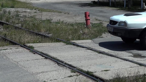 White car passing railway to a fenced place 1 Footage