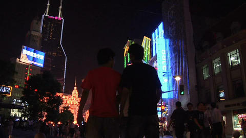 Colorful Neon Signs on Nanjing Road East with Pedestrian strolling in the Evenin Live Action