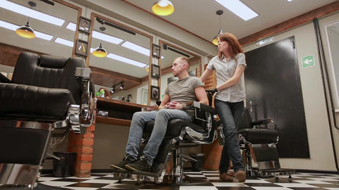 A woman Barber in the barbershop shop to put customer's man in a chair and Archivo
