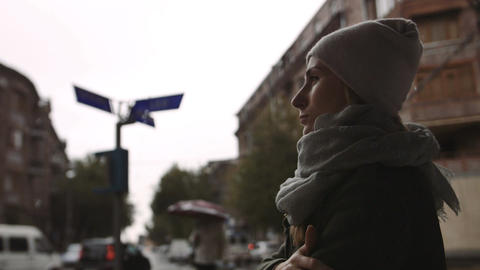 depressed young woman looks at the street on a rainy evening in the town Footage