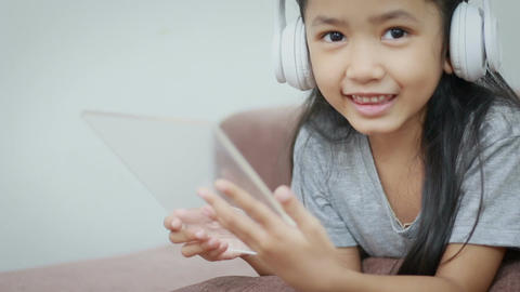 Asian little girl using white wireless headphone and clear pad for futuristic Footage