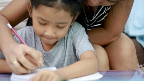 Close up shot Asian little girl doing homework and her mother teach 002 Footage