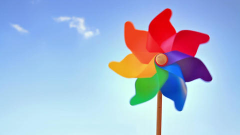 Colorful pinwheel toy against blue sky and clouds Image