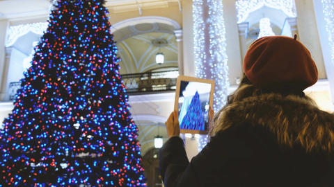 Attractive young girl taking pictures with a tablet Christmas tree Footage