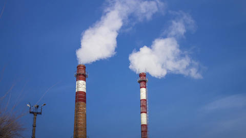 Smoking chimneys of a factory against the sky, the steam from the boiler pipes, Footage