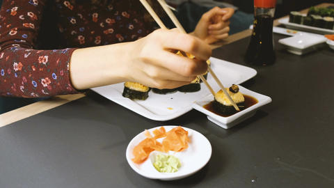 Beautiful Caucasian woman eating sushi in a Japanese restaurant Footage