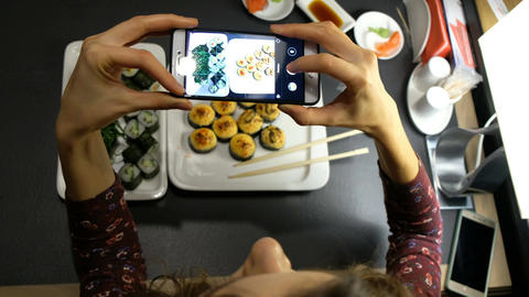 Woman photographing food served in sushi bar with mobile phone. Food and drink Footage