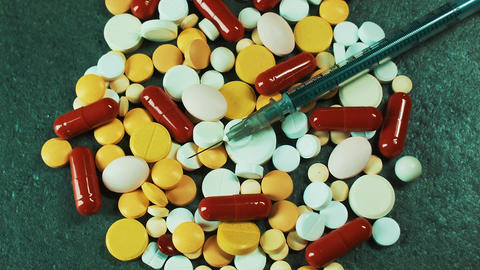 Pharmaceuticals for the treatment of disease. Tablets, pills and a syringe with Footage